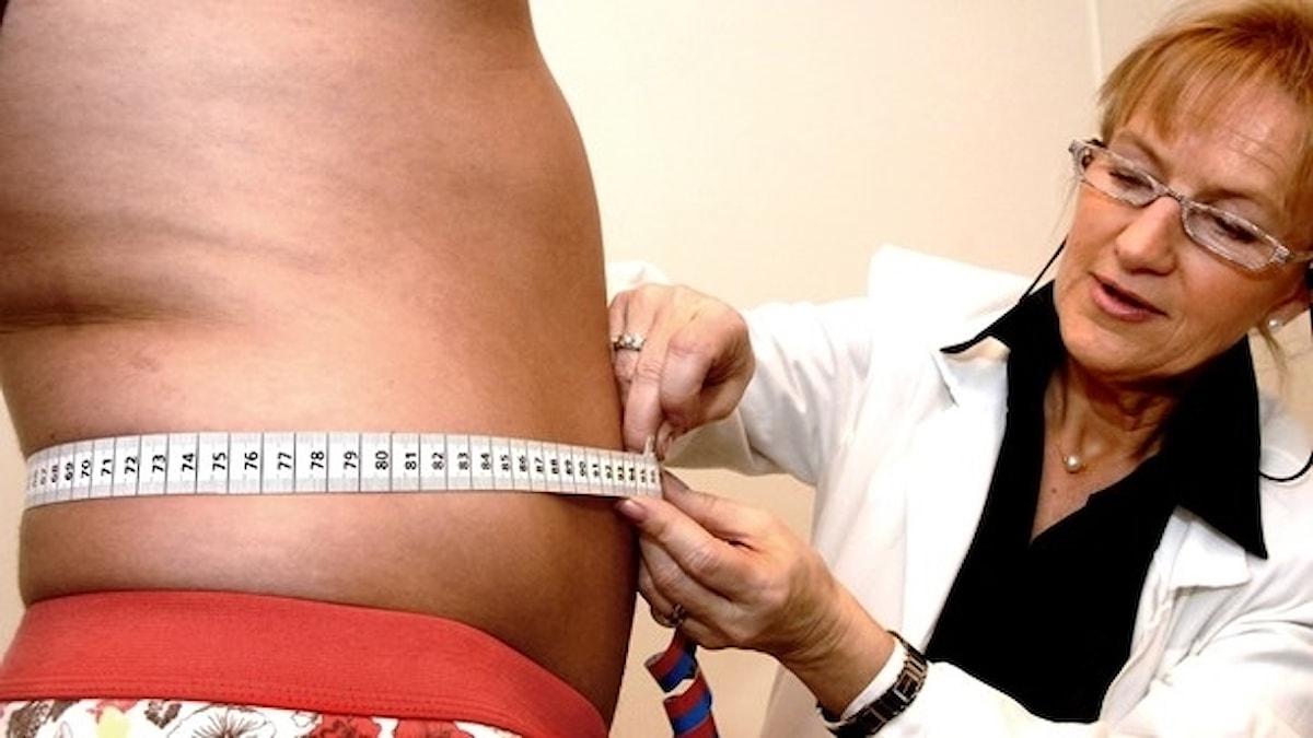 En kvinnlig läkare mäter magen på en tjock man.