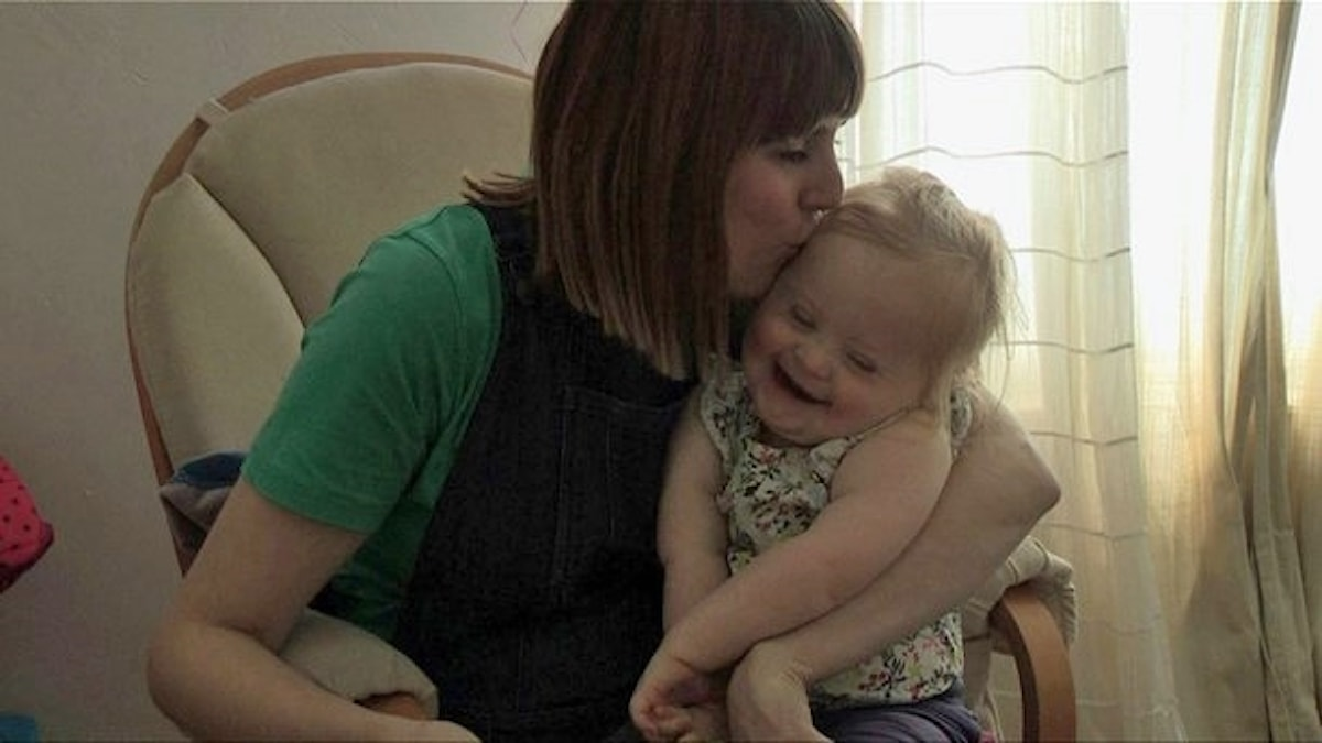 På fotot pussar en mamma sin dotter. Dottern har Downs syndrom.