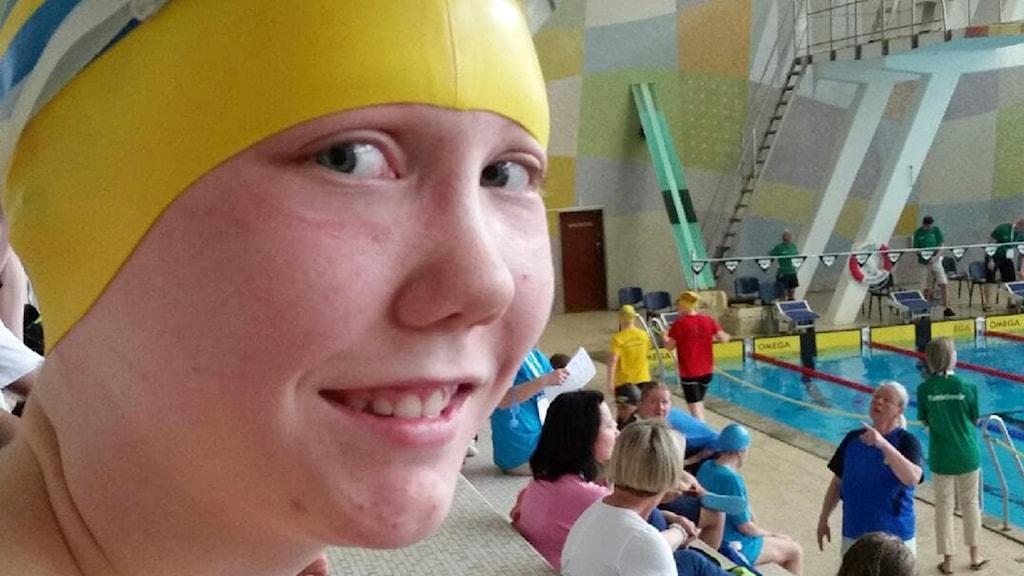 På fotot syns en ung tjej med gul badmössa. I bakgrunden syns en simbassäng.