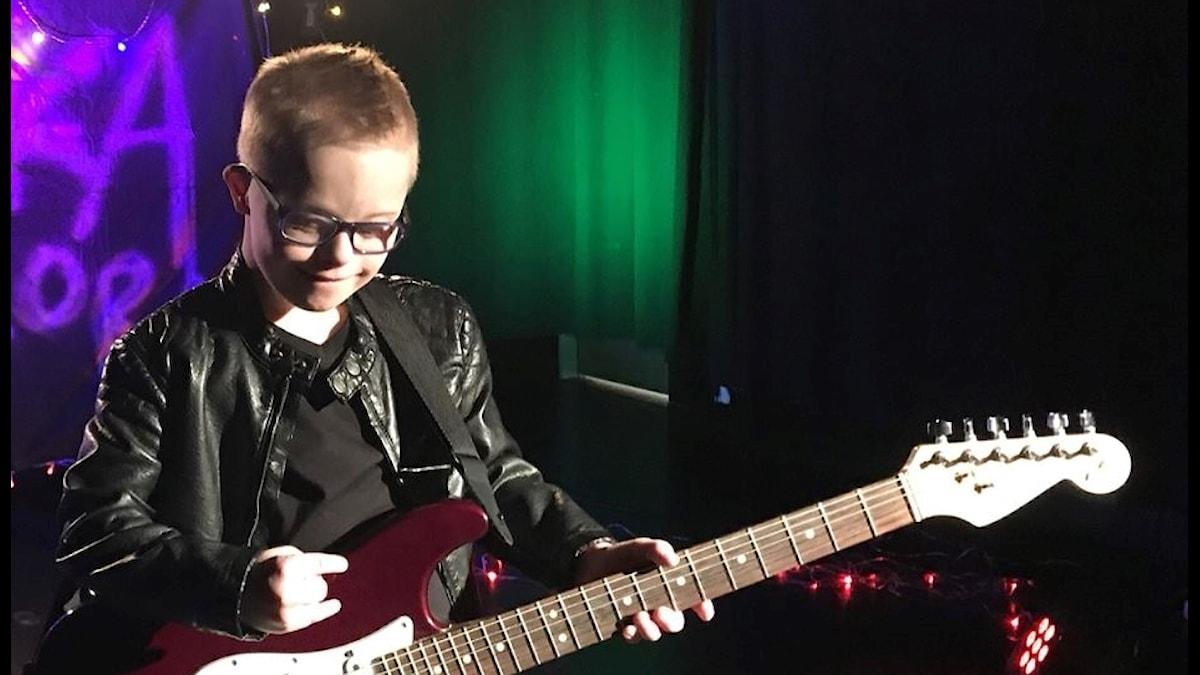 Foto av Max Övik med skinnjacka och elgitarr.