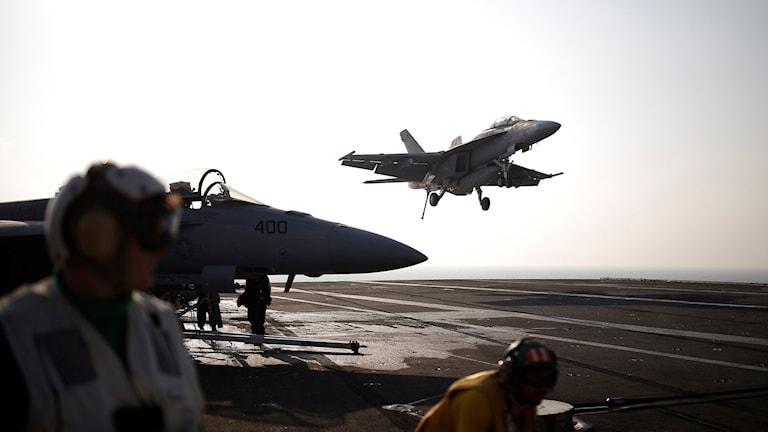 Amerikanska stridsflygplan startar ute på ett stort militärfartyg.