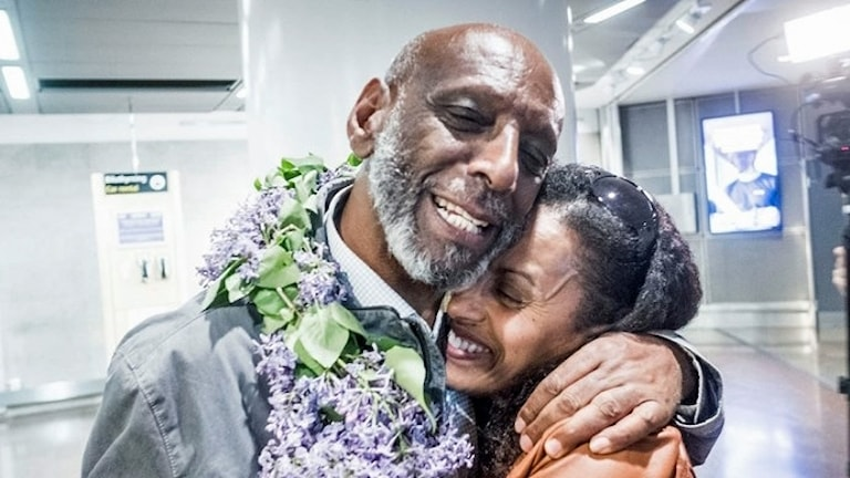På fotot kramas pappan och dottern. Båda ser glada ut. Pappan har en blomsterkrans runt halsen.