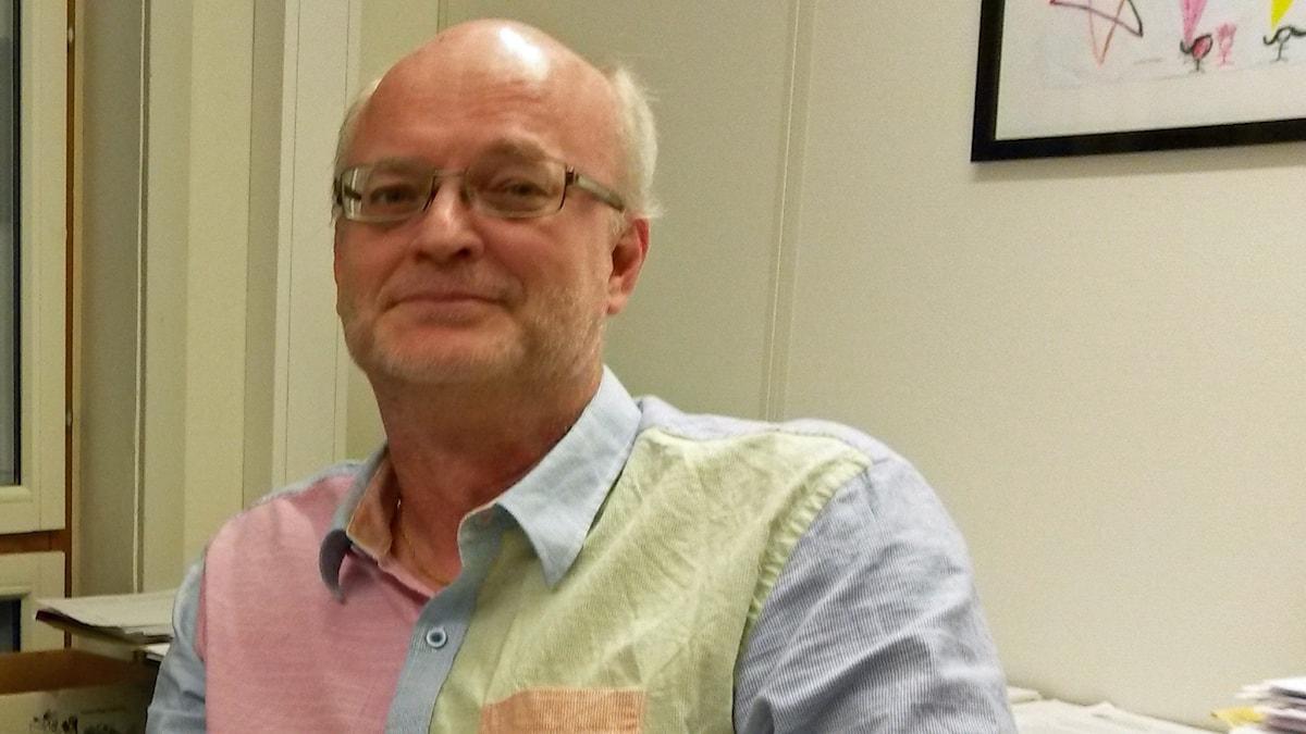 På fotot är Thomas Jansson klädd i en skjorta med olika färger. Han ar glasögon.