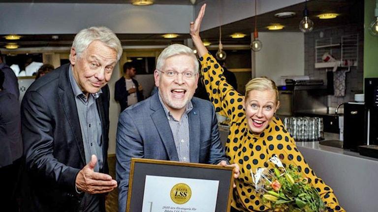 På fotot ser man tre personer som ser glada och spexiga ut. Ola håller i ett diplom och Anna i en bukett blommor.