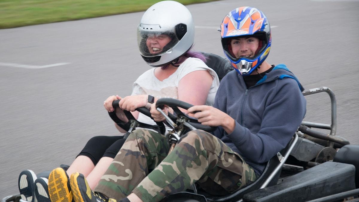 Bilden visar två personer som kör gocart. De håller i varsin ratt och sitter i samma bil. De skrattar och har hjälm på sig.