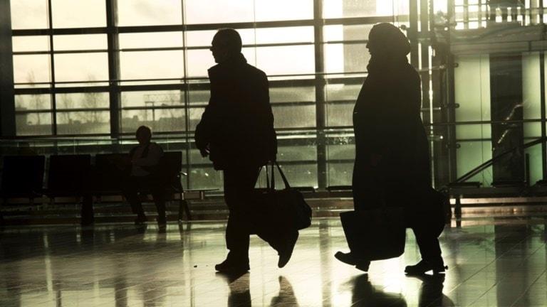 På fotot ser man en man och en kvinna på en flygplats. Bilden är tagen i motljus så deras ansiken syns inte. Kvinnan har en slöja över håret.