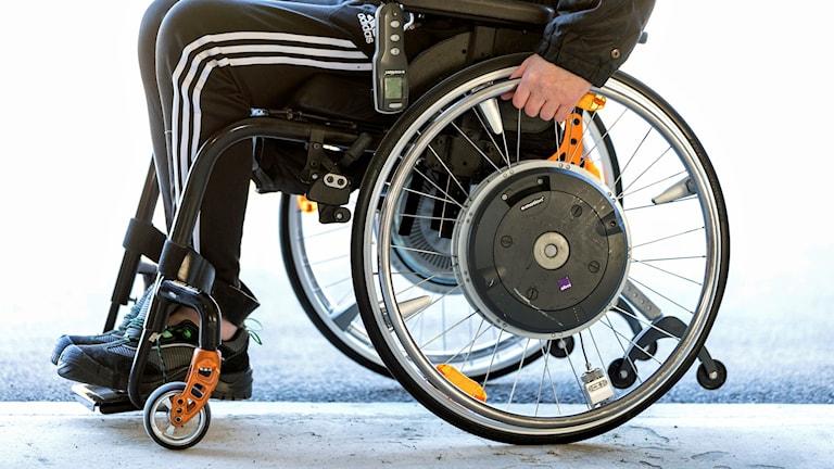 På fotot syns en man som sitter i rullstol, men man ser inte hans ansikte.