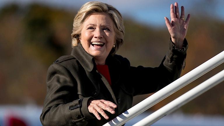 Hon går ombord på ett flygplan och vinkar.