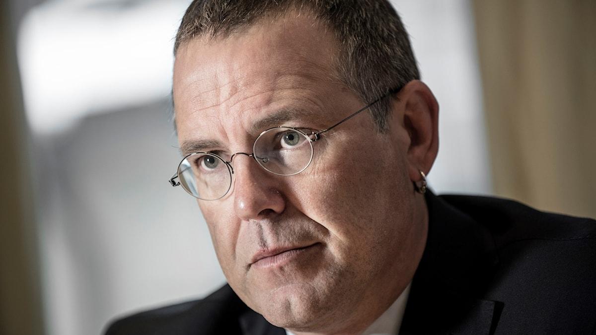 Anders Borg är kortklippt och har runda glasögon. Han har ring i örat.