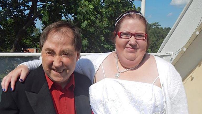 Anders har röd skjorta och svart rock. Sara har en vit brudklänning.