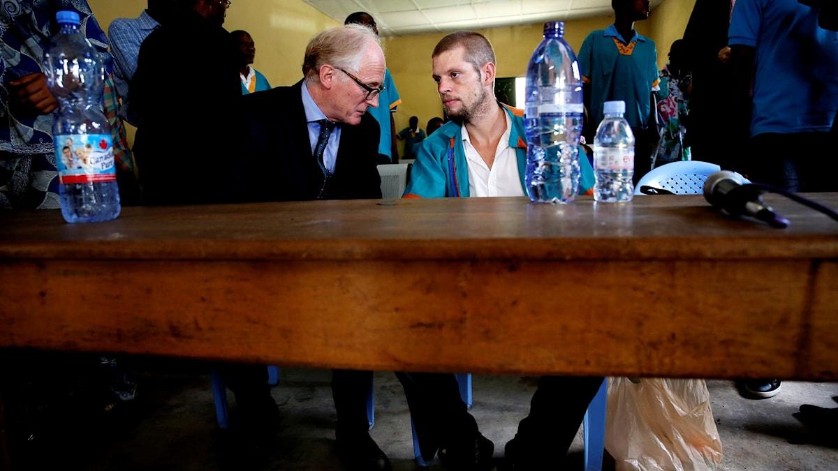 En äldre man från Norges ambassad i Kongo-Kinshasa pratar med Joshua French i domstolen.