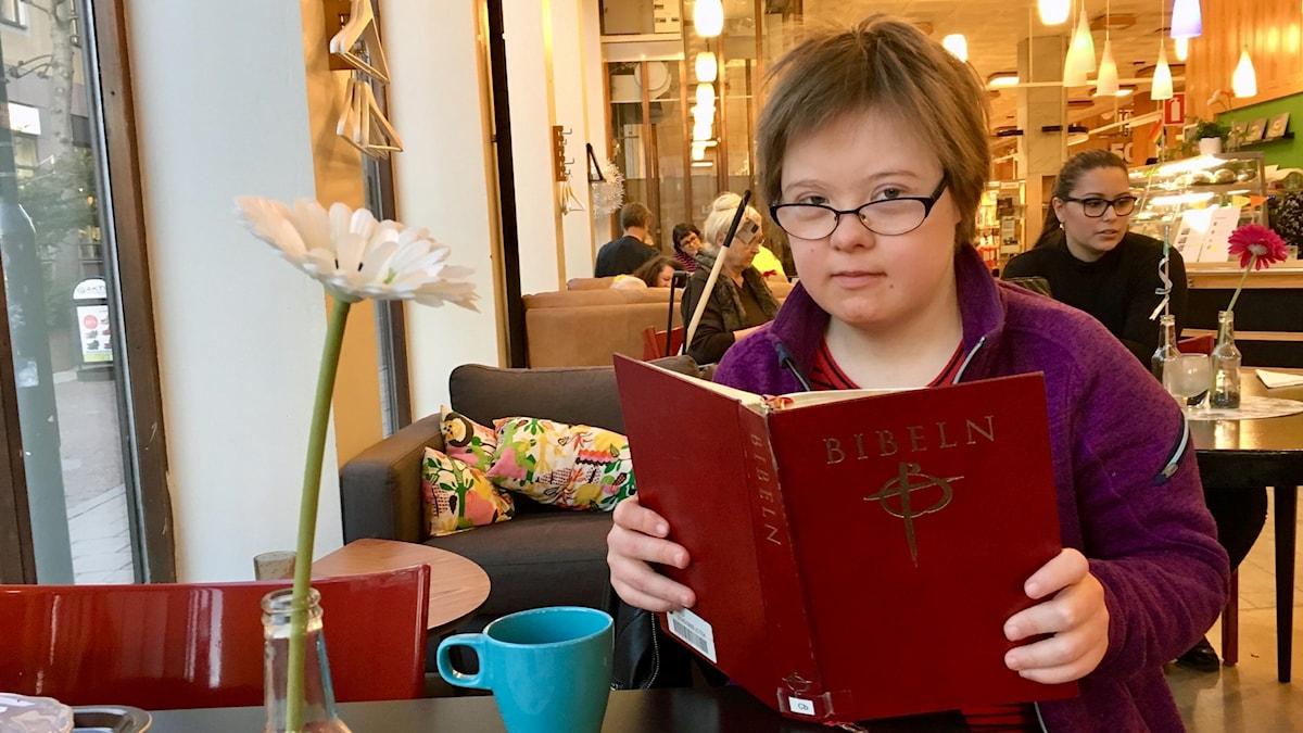På fotot håller Johanna upp en stor röd bok. Hon är på ett kafé.