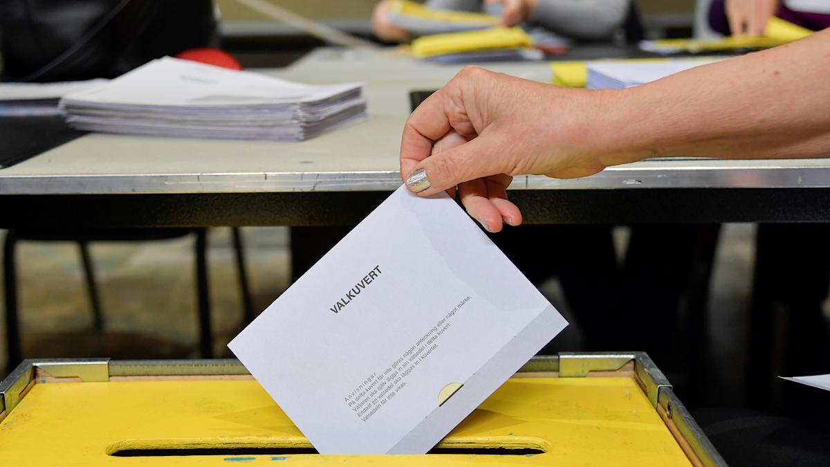 En hand släpper ned en röstsedel i en valurna.