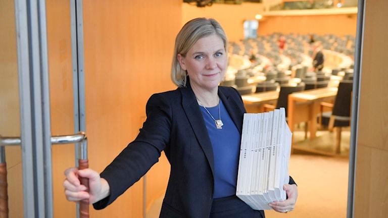 På fotot öppnar Magdalena Andersson en dörr. Hon har en tjock bunt med papper i famnen.