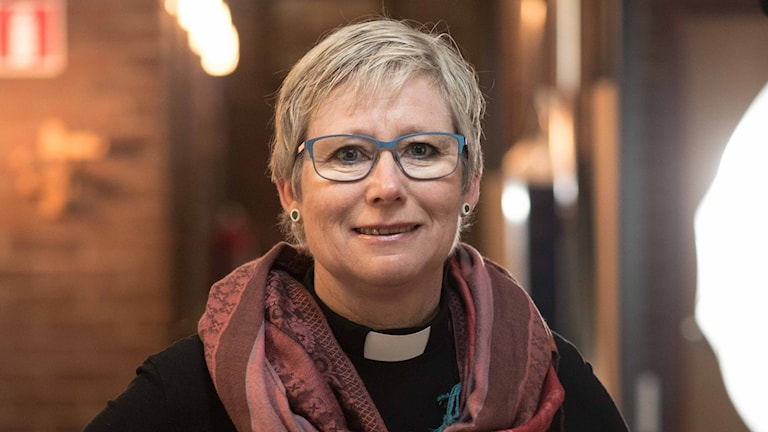 Fotot visar Susanne Rappmann. Hon har en särskild skjorta på sig som visar att hon är präst. Hon har glasögon och kortklippt blont hår.
