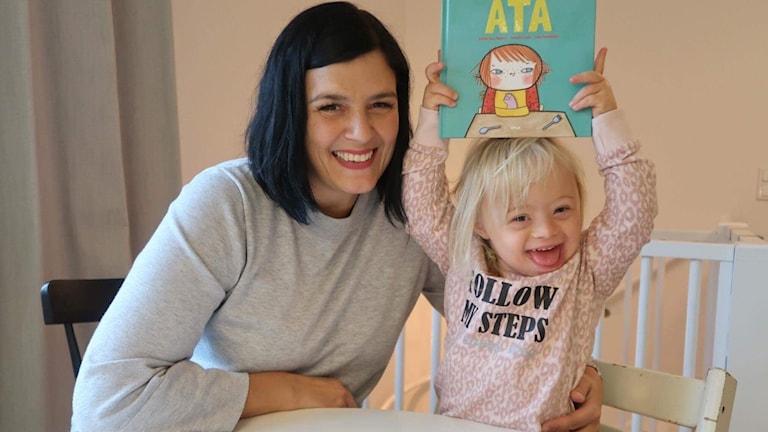 Foto på Linda och Adelina vid ett bord. Adelina håller i en bok.