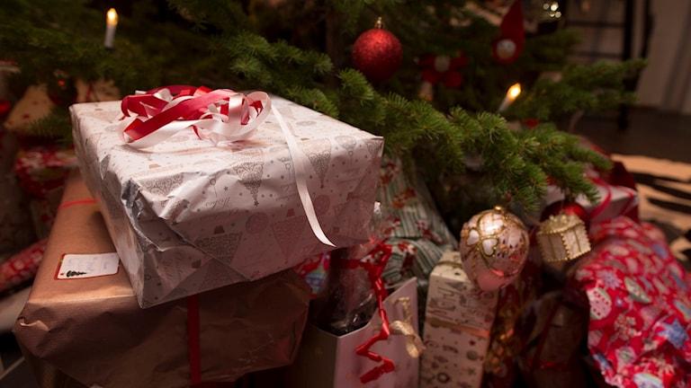På fotot syns en julgran med julklappar under.