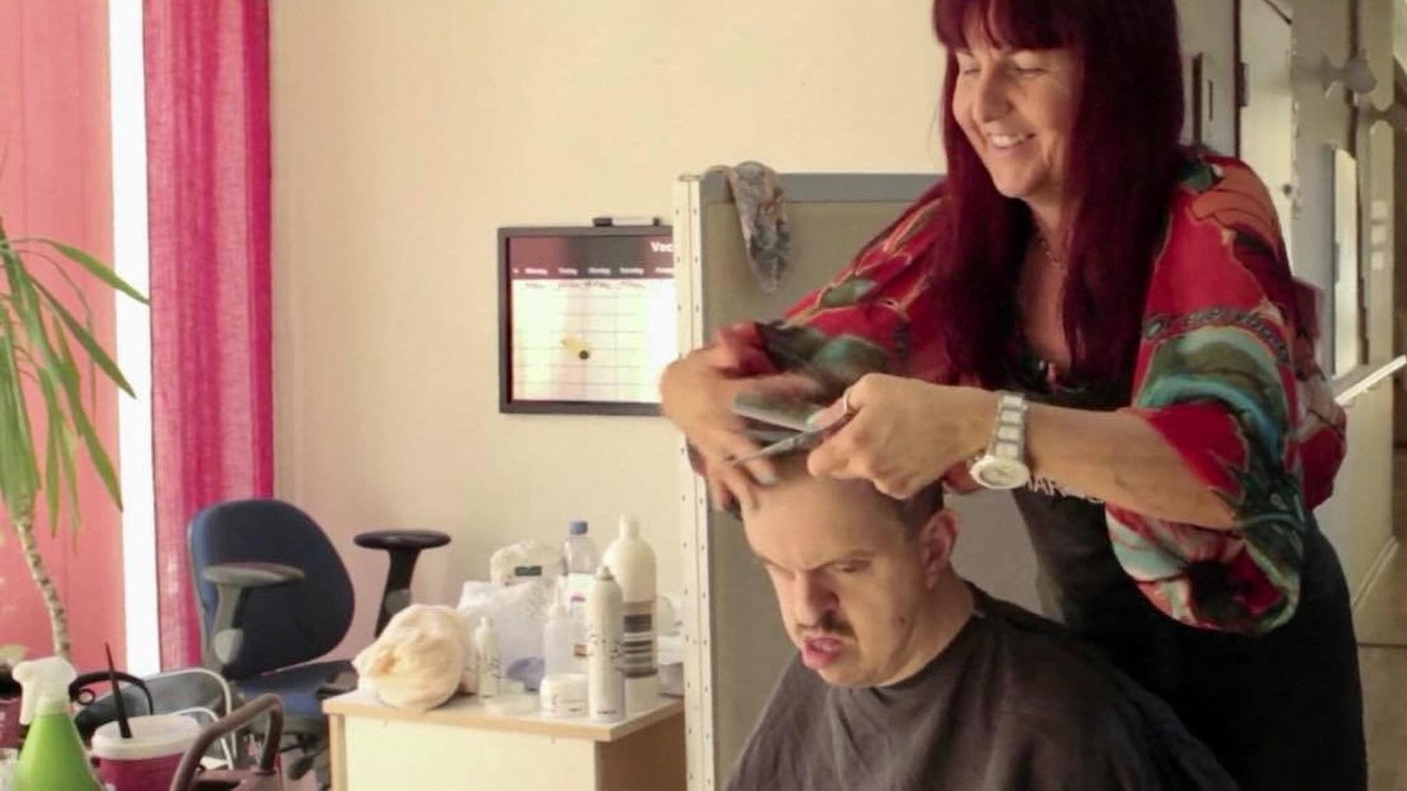 """Bild från filmen """"Klippningen"""" där frisören Maria Jansson klipper sin bror Jocke Mattsson på hans gruppboende på Åland."""