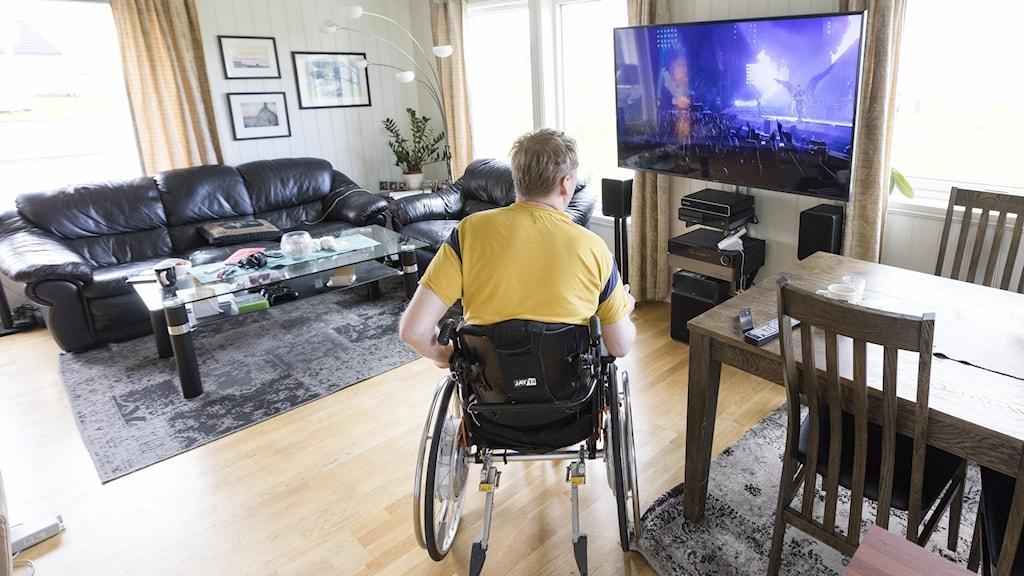 På fotot sitter en ung man i rullstol och tittar på teve.
