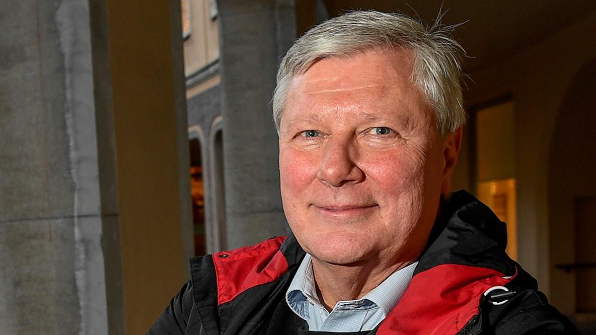 På fotot står Lars Ohly utomhus. Hans jacka är mörkblå med röda detaljer och han har en ljusblå skjorta