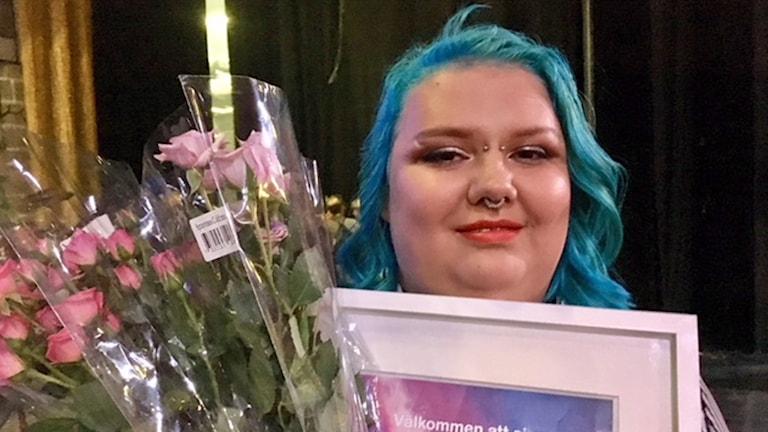 På fotot håller Freja upp ett diplom och blommor.
