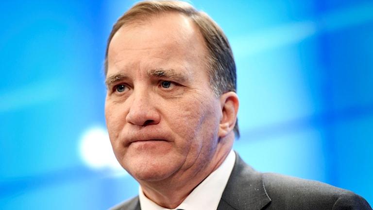 Fotot visar en man i kort mörkt hår, som ser mycket allvarlig ut.