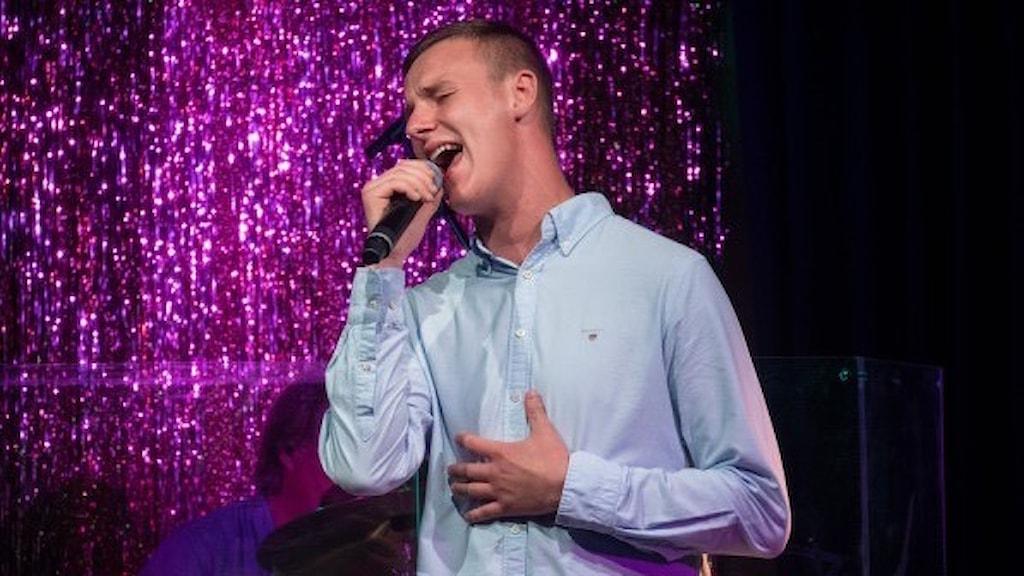 Alex Kron sjunger i en mikrofon. Han har kort ljusbrunt hår och ljusblå skjorta.