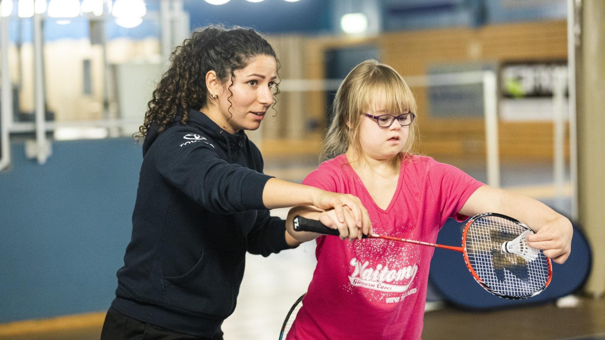 Paniz Yousefi tränar en flicka i att spela badminton. Flickan har Downs syndrom och håller i ett badminton-racket.