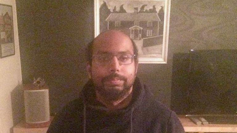 På fotot syns en man med skägg och glasögon.