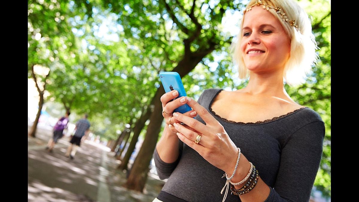 En blond tjej surfar på sin mobiltelefon