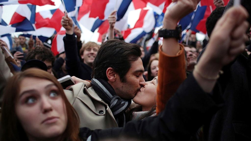 Människor pussas och ler med franska flaggor i rött, vitt och blått för att fira Macron