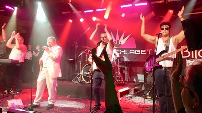 På fotot ser man hur bandet står på scenen och klappar händer.
