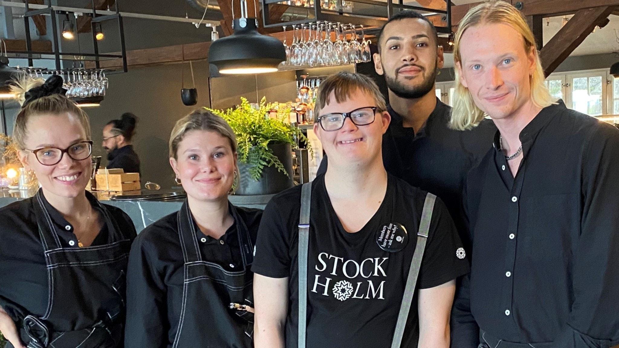 Johan omgiven av sina arbetskamrater i restaurangen på museet där han jobbar. Johan har glasögon och en svart t-shirt på sig.