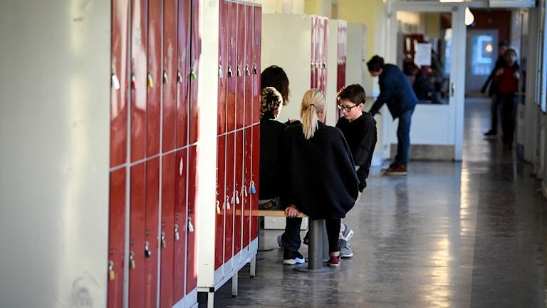 En grupp ungdomar sitter vid ett bord i en skolkorridor. På sidan syns röda skåp.