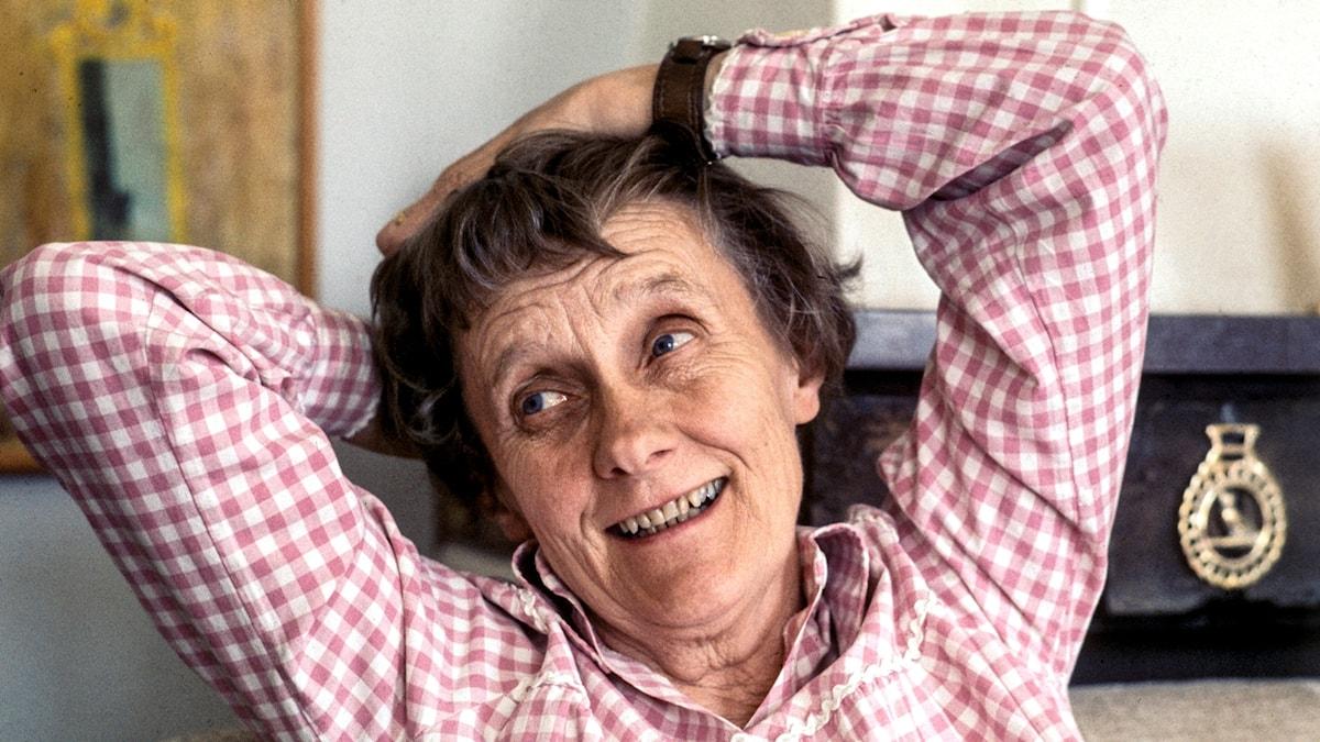 På fotot ser Astrid Lindgren glad ut. Hon håller händerna bakom huvudet och lutar sig bakåt.