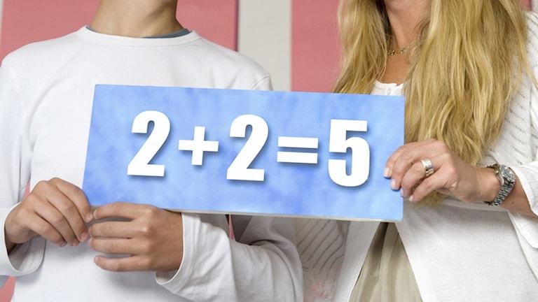 """På fotot syns en skylt med texten """"2+2=5"""". Skylten hålls av en ung kille och en medelålders kvinna. Man ser bara deras händer."""