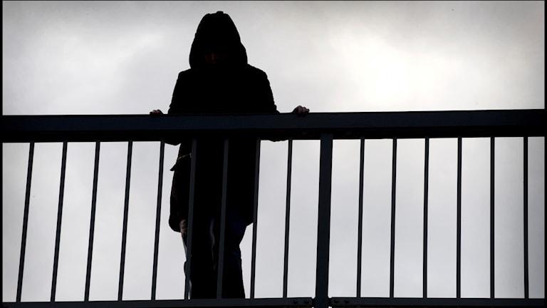 På fotot står en svartklädd person på en bro vid ett räcke.