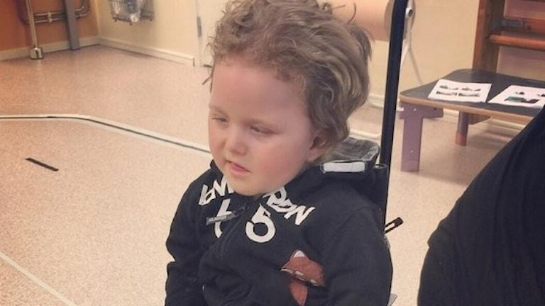 Ludwig sitter i en rullstol. Han har ljust hår som är lite lockigt.