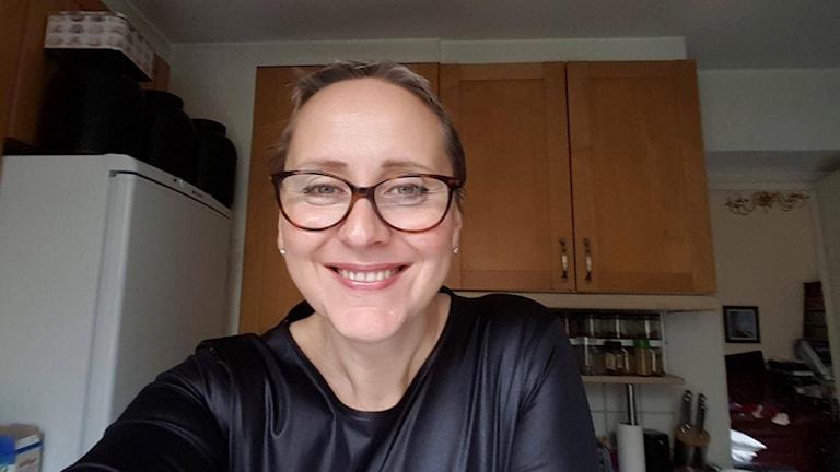 På fotot syns en kvinna, Katy Lock, med glasögon och en svart topp som sitter i ett kök.