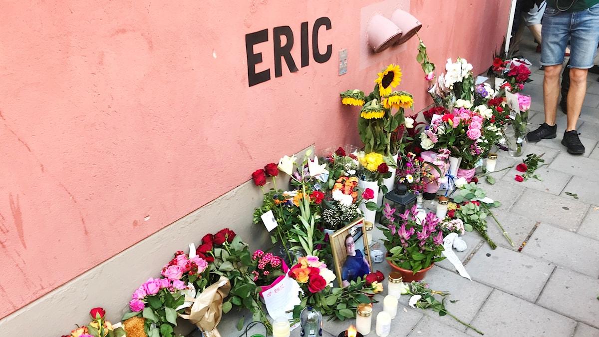 """På fotot syns blommor och tända ljus. På husväggen står det skrivet """"Eric""""."""