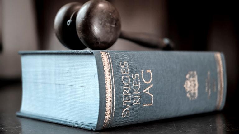 På fotot syns en lagbok, som är blå med guldfärgad skrift, och ovanpå boken ligger en ordförandeklubba av trä.