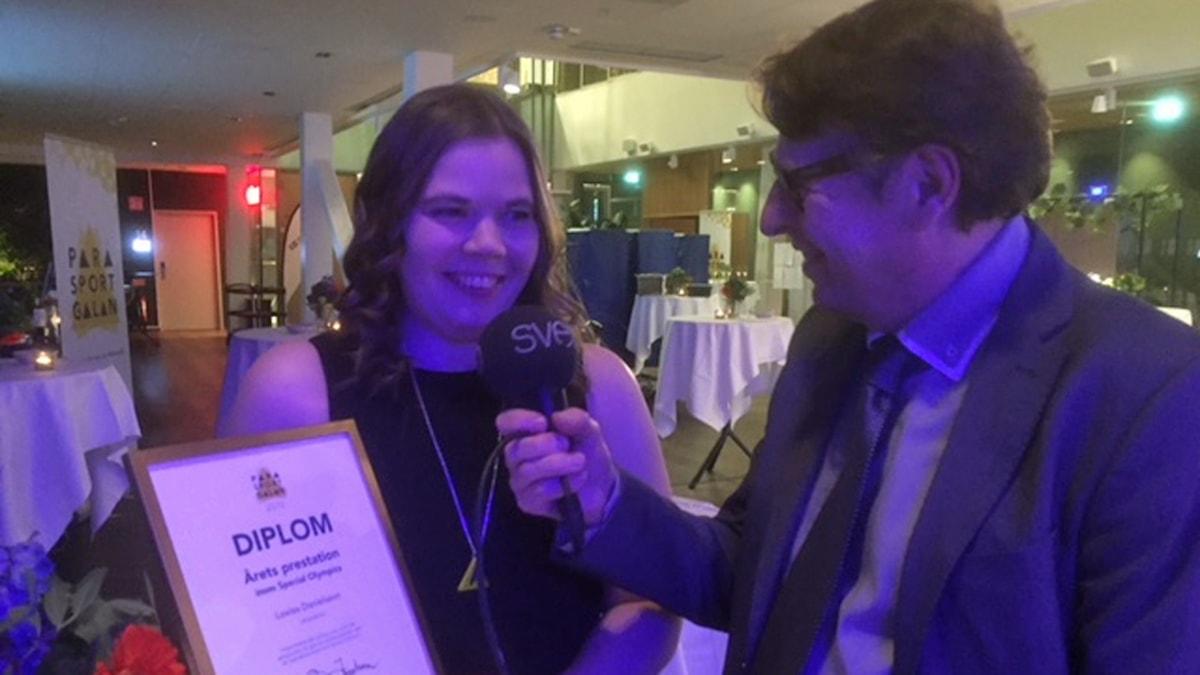 På fotot håller Lovisa upp ett diplom samtidigt som reportern sticker fram sin mikrofon.