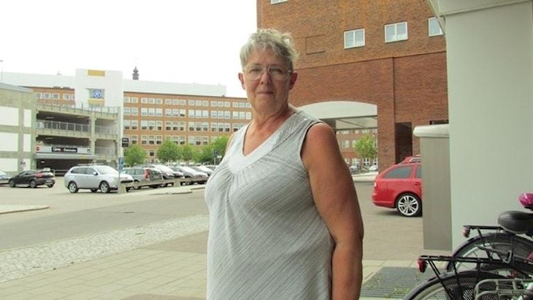 En kvinna i vit klänning, kort hår och glasögon.
