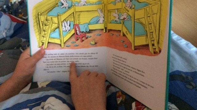"""Ett barn läser boken """"Pricken"""" och pekar i texten"""