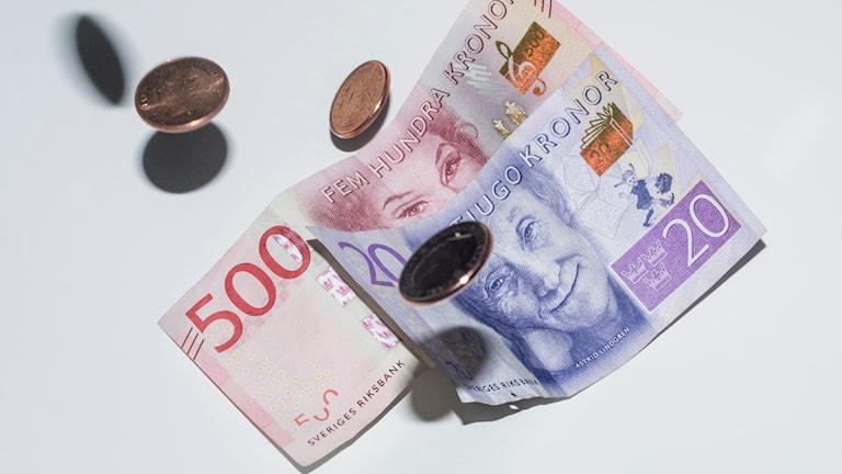 På fotot syns svenska sedlar och mynt.