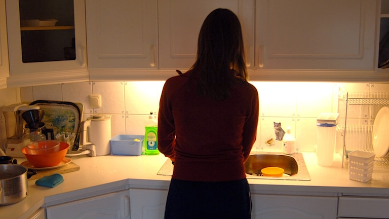 På fotot ser man en kvinna som står vid diskbänken. Hennes ansikte syns inte.