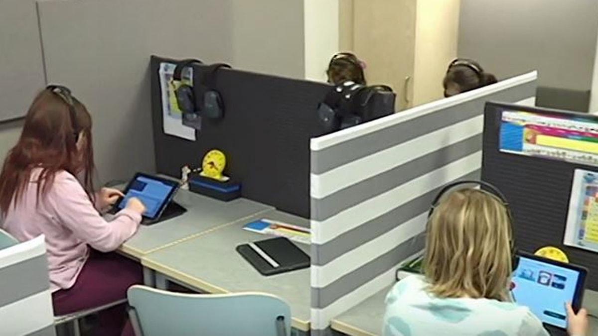 På fotot syns elever som har lurar för öronen. De har också skärmar så att de slipper se varandra.