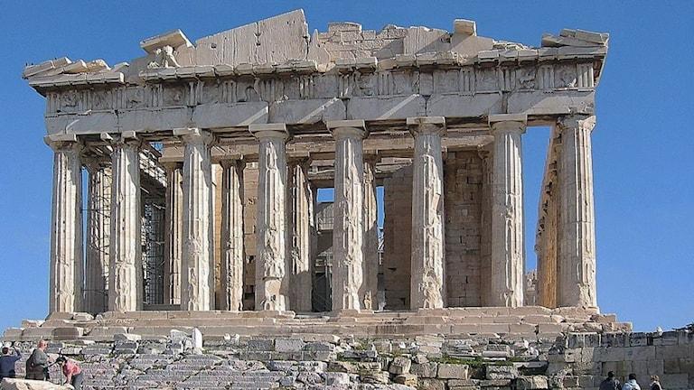 På fotot syns ett tempel som är byggt i vit sten. Man ser en lång rad pelare och resterna av ett tak.