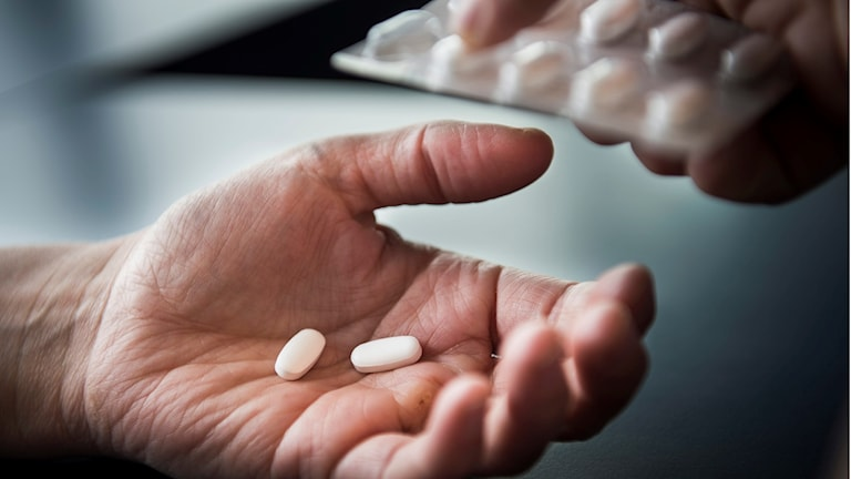 På fotot ser man en utsträckt hand där någon har lagt två tabletter.