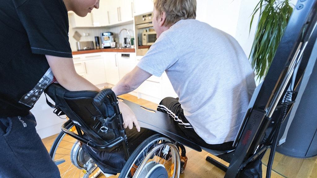 På bilden ser man man i en stol som får hjälp att flytta över till en rullstol.